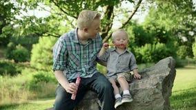 Gene com suas bolhas de sabão de sopro do filho, passatempo da família do divertimento, uma criança que tem o divertimento com se filme