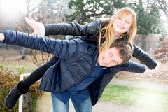 Gene Daddy e a filha que jogam às cavalitas o outono exterior imagens de stock royalty free