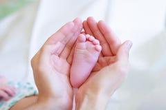 Gene delicadamente o pé do bebê da preensão em suas mãos #2 foto de stock