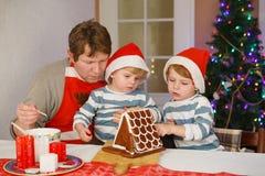 Gene e dois filhos pequenos que decoram uma casa da cookie do pão-de-espécie Imagens de Stock Royalty Free