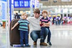 Gene e dois meninos pequenos do irmão no aeroporto Imagens de Stock