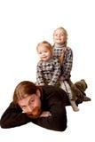 Gene e duas crianças que sentam-se sobre para trás de seu pai. Imagens de Stock