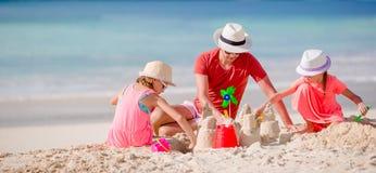 Gene e duas meninas que jogam com a areia na praia tropical Imagens de Stock Royalty Free