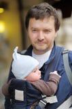 Gene e seu bebê em um portador de bebê Fotos de Stock