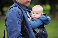 Gene e seu bebê em um portador de bebê Fotografia de Stock Royalty Free