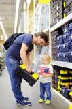 Gene e seu filho que escolhe a caixa de ferramentas direita na em uma loja de ferragens Imagem de Stock Royalty Free