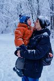 Gene e seu filho que jogam fora, floresta do inverno no fundo, nevando, feliz e alegre imagens de stock