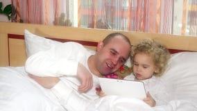 Gene e sua filha bonito que encontra-se na cama que olha na tabuleta digital filme
