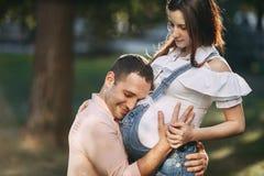 Gene a espera para o bebê que abraça sua barriga da esposa imagens de stock