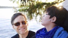 Gene a fala com o filho deficiente na cadeira de rodas no lago Foto de Stock