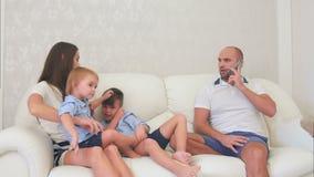 Gene a fala ocupada no telefone quando os rapazes pequenos que jogam com sua mãe no sofá vídeos de arquivo