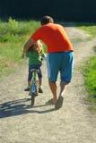 Gene a filha de ensino para montar uma bicicleta em uma estrada secundária empoeirada Fotografia de Stock Royalty Free