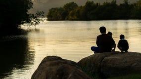 Gene a filha seu filho, sentando-se nas rochas no parque Fotos de Stock