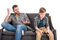 Gene gesticular e falar ao filho pequeno que senta-se no sofá e que usa o smartphone imagens de stock