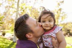Gene guardar e beijar sua filha nova em um parque fotos de stock