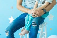 Gene guardar a mão de seu filho que senta-se no fundo do azul do estúdio Mãos do close-up do homem do menino e do adulto imagens de stock