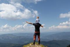 Gene guardar a menina em seu ombro quando sobre a montanha Dia de verão ensolarado foto de stock royalty free
