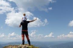 Gene guardar a menina em seu ombro quando sobre a montanha Dia de verão ensolarado fotos de stock royalty free
