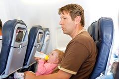 Gene guardar sua filha do beb? durante o voo no avi?o que vai em f?rias fotos de stock royalty free