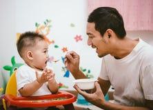 Gene mamã ativa que alimenta seu bebê de um ano do bebê do filho na cadeira fotos de stock royalty free