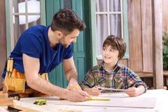 Gene mostrando ao filho como tomar medidas da prancha de madeira imagem de stock royalty free