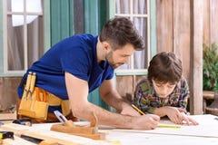 Gene mostrando ao filho como tomar medidas da prancha de madeira fotografia de stock