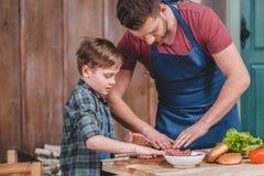 Gene no avental e no filho pequeno bonito que preparam hamburgueres junto fotografia de stock royalty free