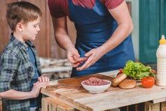 Gene no avental e no filho pequeno bonito que preparam hamburgueres junto imagem de stock royalty free