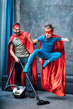 Gene no tapete limpando do traje do super-herói quando filho no salto do traje do super-herói Imagem de Stock