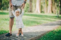 Gene o bebê de ensino para andar no parque imagem de stock royalty free