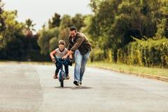 Gene o ensino de seu filho montar uma bicicleta foto de stock royalty free
