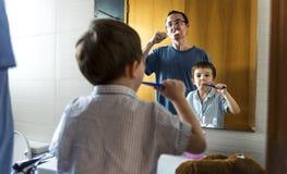 Gene o filho de ensino como escovar seus dentes fotos de stock royalty free