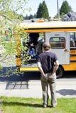 Gene o filho deficiente de espera para sair o ônibus escolar foto de stock royalty free
