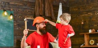 Gene, parent com a barba no filho de ensino do capacete protetor para usar ferramentas diferentes na oficina da escola fatherhood foto de stock