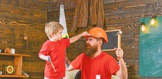 Gene, parent com a barba no filho de ensino do capacete protetor para usar ferramentas diferentes na oficina da escola fatherhood imagens de stock