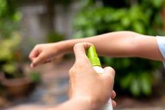 Gene repelentes de insetos de pulverização em seu braço do filho no jardim imagens de stock