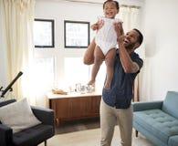 Gene Standing In Lounge em casa que levanta a filha do bebê no ar imagem de stock royalty free