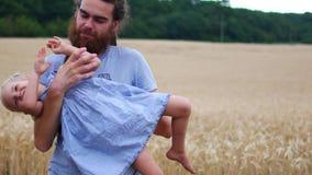 Gene ter o divertimento que guarda sua filha loura pequena nos braços vídeos de arquivo