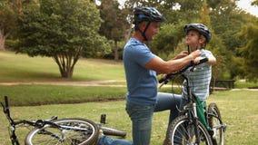 Gene a união de seu capacete do ciclismo do filho no parque filme