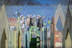 GENEBRA, SUÍÇA - EM FEVEREIRO DE 2019 - caminhada da mulher perto da pintura mural do campo de jogos da escola de Grottes junto a foto de stock royalty free