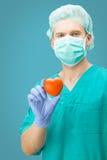 Geneeskunde en gezondheidszorg - het stuk speelgoed van de chirurgenholding hart met één hand op lichtblauwe achtergrond Stock Foto