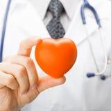 Geneeskunde en gezondheidszorgsymbolen - het stuk speelgoed van de artsenholding hart met twee vingers stock afbeeldingen