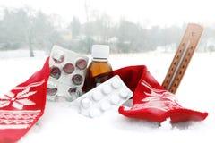 Geneeskunde met stroop en rode sjaal in sneeuw en thermometer stock afbeelding