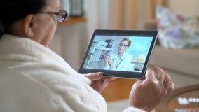Geneeskunde online Bejaarde die haar arts raadplegen die videopraatje thuis gebruiken stock video