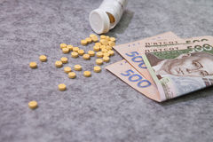 Geneeskunde, pillen, geld, op een grijze achtergrond, Oekraïense hryvnia Royalty-vrije Stock Foto's