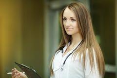 geneeskunde Portret van een glimlachende jonge verpleegster met een vage patiënt in de het ziekenhuisgang Koele kleren Arts Huisa stock afbeeldingen