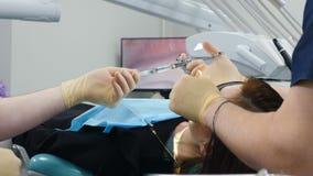 Geneeskunde, tandarts, en gezondheidszorgconcept De medewerker geeft op spuit aan een tandarts Close Het voorbereiden van injecte stock video