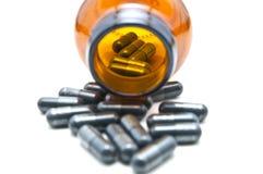 Geneeskundecapsule in fles op wit Stock Foto's