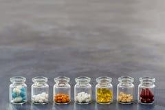 Geneeskundeconcept: lijn van Geneeskundetabletten in geopende glasfles met multi gekleurde plastic kappen op leiachtergrond Stock Foto's