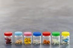 Geneeskundeconcept: lijn van Geneeskundetabletten in glasfles met multi gekleurde plastic kappen op leiachtergrond Royalty-vrije Stock Fotografie